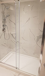 shower with sliding glass door and custom tiles